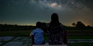Silhouettes of a mother and child, sitting outside in nature under a starry sky.