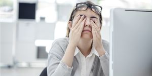 A woman sits at her desk at work in front of her computer and is rubbing her eyes to relieve eyestrain