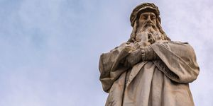 A statue of Leonardo da Vinci, who may have had strabismus, seen against a blue sky.