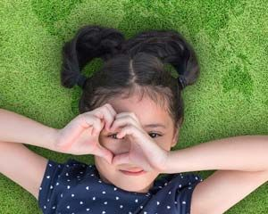 Photograph of a girl on the grass looking through her fingers