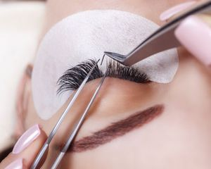 Closeup of a single eyelash extension being placed in eyelashes of a person, using tweezers.
