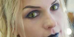 Woman wearing green cat-eye costume contact lenses.