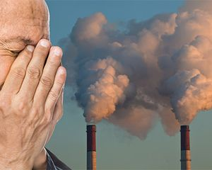 Man covering his eyes and nose with his hands in front of smoke stacks with pollution coming out of them