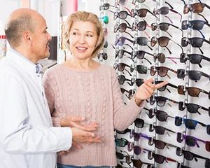 Photograph of a woman selecting sunglasses
