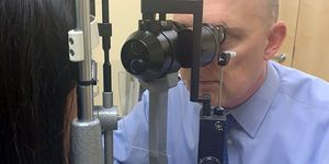 Ophthalmologist uses slit-lamp breath shield during coronavirus COVID-19 outbreak