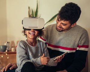 Parent and child at home with virtual reality headset.
