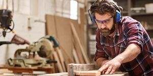 Carpenter wearing goggles while operating a table saw.