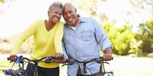 An older couple pose with their bicycles outside on a sunny day.