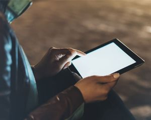 Person holding tablet computer outdoors at night.