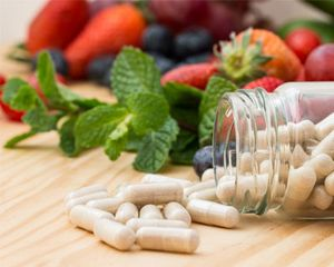 Nutritional supplement pills and fruit on wooden table.