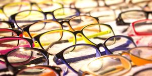 Close-up of many pairs of eyeglasses arranged on a lighted table.