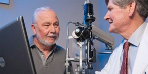A man sits and consults with his ophthalmologist discussing his eye health.