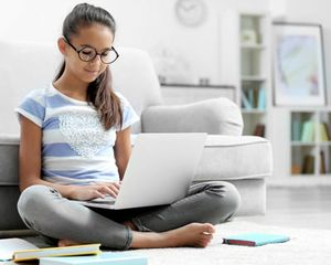 Young girl sitting on the floor at home, wearing glasses and looking at laptop computer.