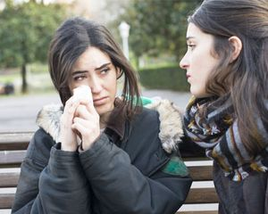 Woman crying on park bench and being comforted by a friend.