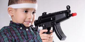 Child holding a toy gun to highlight December Safe Toys Month.