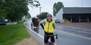 Cyclist Heinz Richardson stands with his bicycle while an Amish horse and buggy go by on the road
