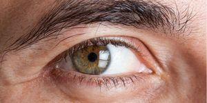 Imagen de primer plano del ojo verde de un hombre adulto