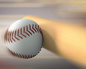 Closeup of a bat hitting a baseball