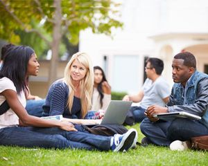 A group of college students sit on grass, with books and laptops.