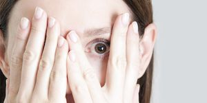 A person covers their face with their hands, with just one eye showing a worried expression.