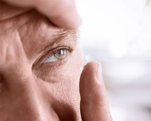 A closeup of a man's face and hand. He has a contact lens on his finger and is about to place the contact on his eye.