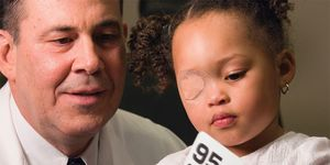 An ophthalmologist sits with a child whose eye is patched