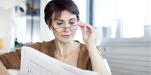 An older woman with newspaper and reading glasses