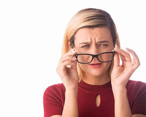 A woman has a problem with her vision and looks at her glasses with confusion.