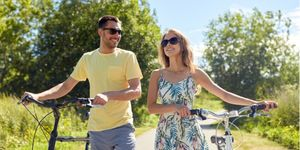 A couple wearing sunglasses standing with bicycles outdoors.