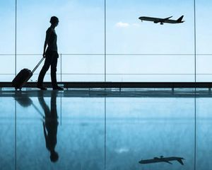 Person in silhouette in airport with airplane taking off in background