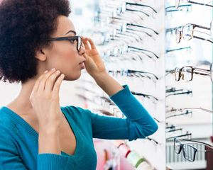 Woman trying on glasses in front of wall of eyeglasses