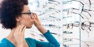 Young woman trying on frames at optical store