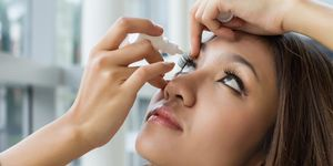A woman puts eye drops in her eye.