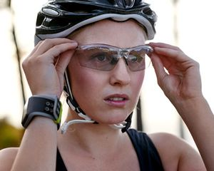 Woman wearing bicycle helmet and putting on protective glasses.