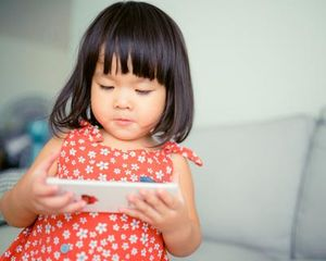 Young girl standing in a livingroom and using a smartphone.
