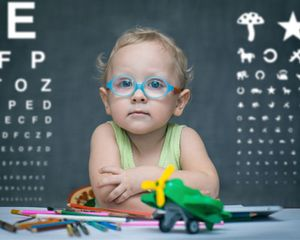 Child in glasses sitting at desk in front of blackboard