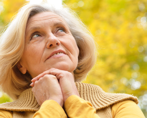 Woman outside looking up at the sky with yellow leaves in background