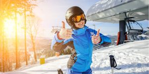 Young smiling girl at ski resort on sunny day giving the thumbs up for the camera before she hits the slopes