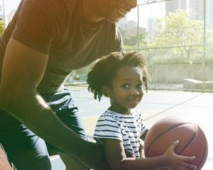 Young girl holding a basketball and playing with her father on an outdoor basketball court.