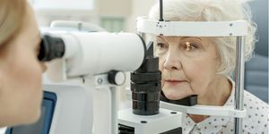 Photo of an ophthalmologist using a slit lamp to look at senior woman's eyes