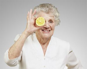 Photograph of a woman holding a slice of lemon