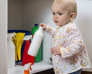 Toddler holding cleaning chemicals from under sink.