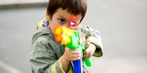 A young boy standing outside aims a large toy rifle at the camera.