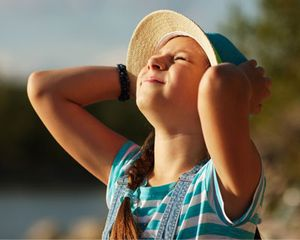 A young girl in hat squints up at sun, looking into the sky.