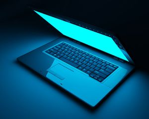 Laptop computer sitting on a table in blue light