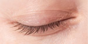 Closeup of a woman's eye with no eye makeup or mascara on eyelashes