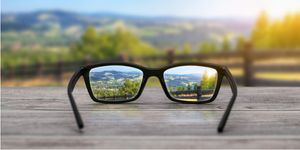 A pair of glasses on a table bring a blurry distance view into focus.