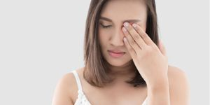 A young woman rubbing her eye, which is irritated from blepharitis