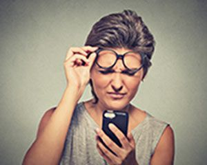 Photograph of woman with glasses trying to see her phone
