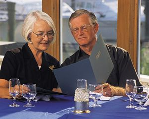 Photograph of older couple reading menu in bright light